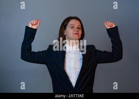 Une femme d'affaires confiante et déterminée qui fléchit les muscles montrant sa force, expression positive du visage. Concept de développement personnel et de motivation. Banque D'Images