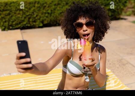 Jeune femme prenant selfie près de la piscine Banque D'Images