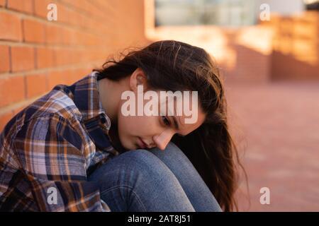 Une adolescente assise dans le domaine scolaire Banque D'Images