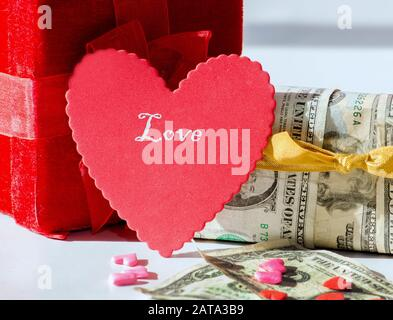 Un coeur rouge et une boîte cadeau de lecture avec une autre boîte enveloppée dans l'argent et les factures et les bonbons au premier plan. Le coût de l'amour Banque D'Images