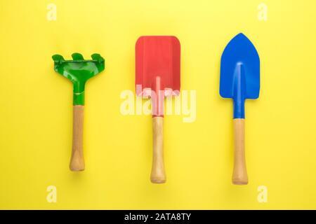 Une couche plate de petits outils de jardin sur fond jaune concept créatif minimal. Banque D'Images