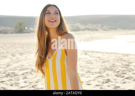 Jolie jeune femme souriante qui aime se détendre le matin sur la plage Banque D'Images