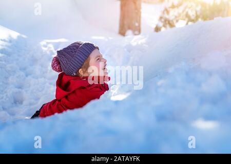 Joyeux enfant dans la neige, jolie petite fille gaie posée dans la pile de neige et de rire, en profitant des vacances d'hiver, heureuse enfance insouciante