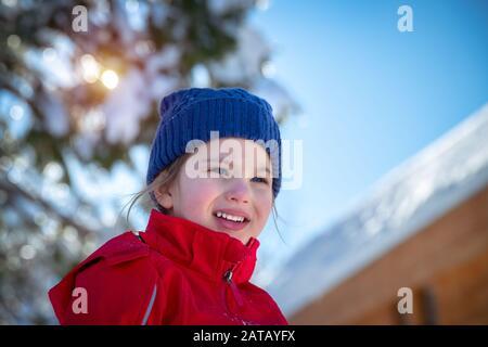 Portrait d'une jolie petite fille qui s'amuse à l'extérieur, un enfant joyeux qui profite d'une journée d'hiver ensoleillée, de bonnes vacances d'hiver Banque D'Images