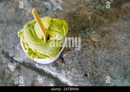 Crème glacée à la pistache sur fond de pierre grise. Crème glacée à la pistache maison dans un bol classique sur une table en béton gris vue sur le dessus espace de copie. Pelle à glace Matcha dans un bol sur fond de pierre grise Banque D'Images