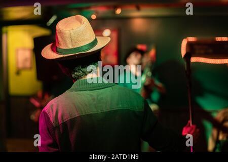 Gros plan du musicien masculin tenant le microphone contre le chant d'artiste sur scène dans la salle lumineuse de l'auditorium au monde et le festival de mots parlés Banque D'Images