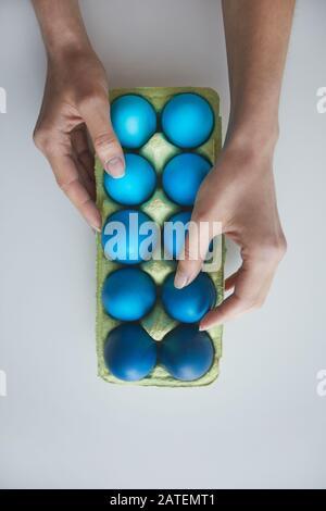 Au-dessus de la vue arrière-plan main féminine organisation de la composition des oeufs de Pâques peints bleus dans la caisse sur blanc, espace de copie