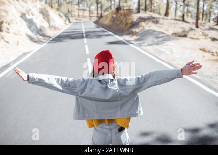 Portrait de style de vie d'une femme élégante courir sur la belle route de montagne, se sentir heureuse et insouciante pendant le voyage. Vue de l'arrière