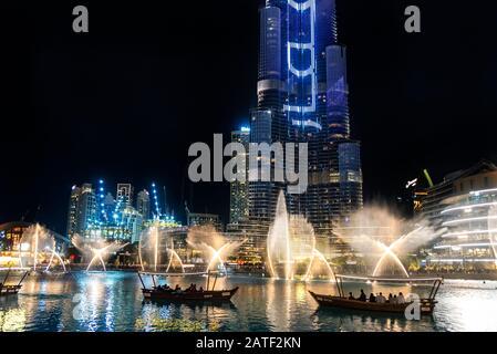 Des bateaux de tourisme qui regardaient la fontaine chorégraphiée à Dubaï la Fontane la nuit se reflète sur l'eau du lac Burj Khalifa Banque D'Images
