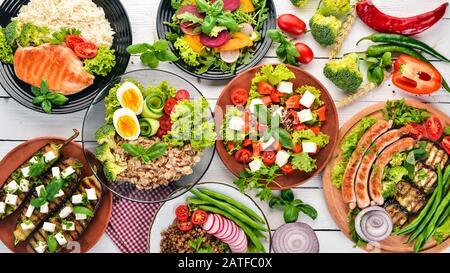 Nourriture. Lentilles, flocons d'avoine, poulet, tomates, saucisses, aubergine. Des aliments sains. Sur une table en bois blanc. Vue de dessus. Espace libre pour le texte. Banque D'Images