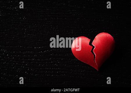 Coeur rouge cassé sur fond en bois noir. Cœur brisé, Amour et Saint Valentin concept de jour. Banque D'Images