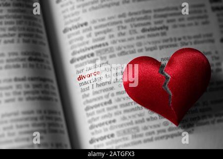 Cœur rouge cassé sur la définition de divorce de dictionnaire. Le concept de divorce, de tronçonnage, d'infidélité . Mise au point sélective. Banque D'Images