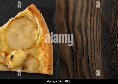 Coupez en tranches de délicieuses pizzas fraîches tortilla avec des poires et du fromage Dor Blue sur fond sombre. Vue de dessus, espace de copie. Banque D'Images
