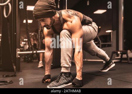 Un homme sportif barbu dans la salle de sport fait des exercices de yoga et d'arts martiaux. Banque D'Images