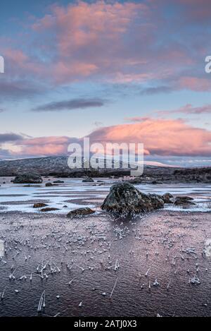 Lever du soleil sur une Lochan na h-achlaise gelée sur Rannoch Moor près de l'entrée de Glencoe dans les Highlands écossais Banque D'Images