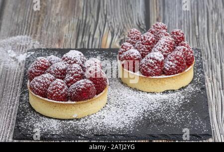 Délicieux mini tartes à la framboise sur fond en bois. Photographie alimentaire