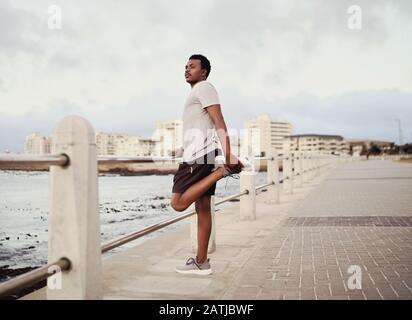 Vue latérale d'un jeune athlète de sexe masculin qui s'étire sur ses jambes à côté de la rampe sur la promenade du bord de mer Banque D'Images