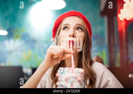 Fille avec des dents blanches, beau sourire en béret rouge, la France boit des milkshake roses de fraise de paille Banque D'Images
