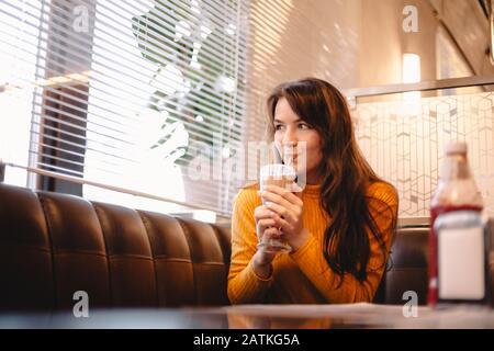 Une adolescente boit du milkshake au chocolat dans le restaurant Banque D'Images