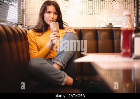 Une adolescente bien réfléchie boit du milkshake au chocolat dans le restaurant Banque D'Images