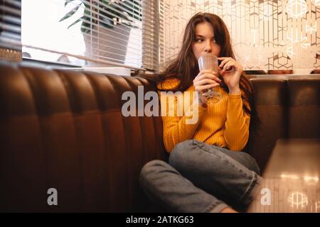 Une adolescente qui boit du chocolat au café Banque D'Images