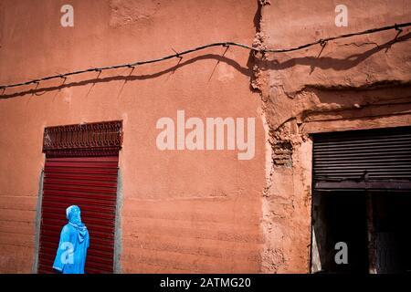 Une femme en vêtements bleus passe devant une porte rouge foncé à Marrakech, Maroc Banque D'Images