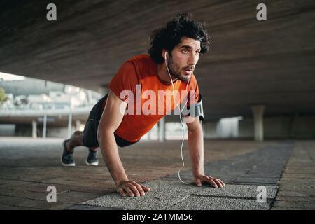 Un homme qui écoute de la musique dans un écouteur fait des exercices de poussée pendant l'entraînement en plein air - un homme qui montre persévérance et détermination