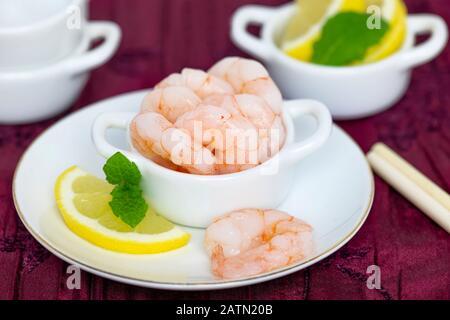 gros plan de crevettes épluchées et cuites entières avec citron et menthe sur un plat, fond flou pour l'espace de copie Banque D'Images