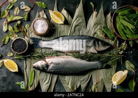 Le poisson frais cru non cuit au bar de la mer sur les feuilles de bambou sèches prêtes à cuire avec du citron, du sel de mer, des haricots noirs et verts, une salade verte sur le béton à texture sombre Banque D'Images