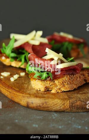 Concept de la cuisine italienne. Bruschetta avec prosciutto, fromage pecorino, salade de roquettes et confiture de figues sur table en bois.
