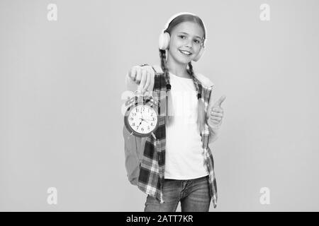 Début des enseignements. Temps aller à l'école. Les heures d'école. Happy girl tenir réveil à compter les minutes. Jour des connaissances. Calendrier des cours. Lycéenne tenir réveil fond jaune. Concept de distribution de l'école. Banque D'Images