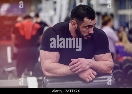 motivation sportive concept de jeune homme barbu fort se détendre parmi les personnes dans la salle de gym pendant l'entraînement de forme physique Banque D'Images