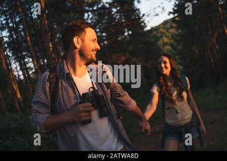 Un couple heureux fait de la randonnée dans la forêt l'après-midi.