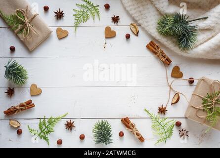 Fond plat. Les boîtes cadeaux sont emballées dans du papier artisanal et présentent un décor simple avec de la cannelle verte et des guavas sur un fond en bois Banque D'Images