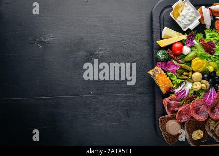 Un grand ensemble de cuisine italienne. Fromage, saucisses, viande et légumes marinés sur carton de bois. Vue de dessus. Espace libre. Banque D'Images