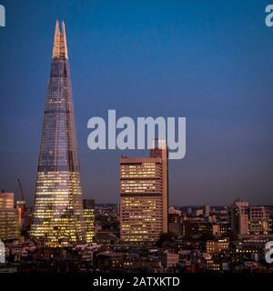 The Shard, Londres. Vue haute angle en soirée du célèbre gratte-ciel Shard illuminé contre un ciel sombre au crépuscule. Banque D'Images