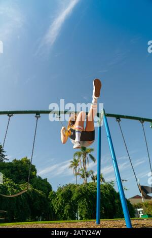 Une adolescente balançant haut dans les équipements de terrain de jeux pour enfants au domaine de Tauranga, en Nouvelle-Zélande.