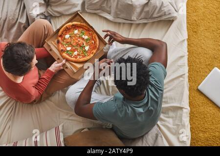 Vue sur le grand angle des jeunes couples assis sur le lit et manger de la pizza ensemble dans la chambre