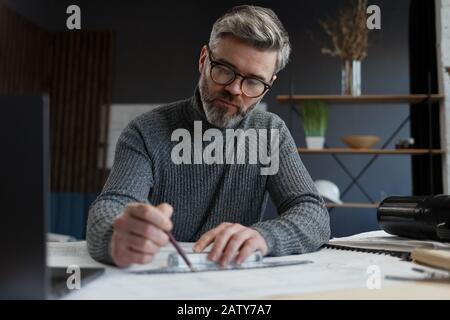 Architecte d'intérieur travaillant au bureau avec des plans.Ingénieur inspecte le plan architectural, esquissant un projet de construction.Portrait de beau barbu Banque D'Images