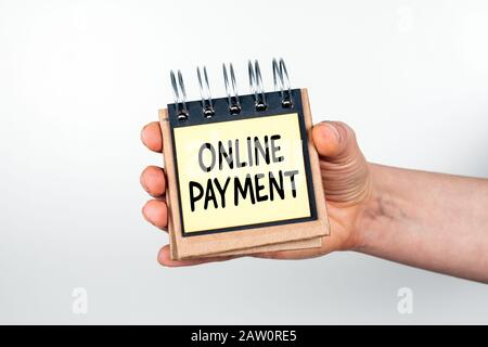Paiement En Ligne. Concept D'Achat, De Vente, De Transfert Et De Transactions Financières. Note livre en main sur fond blanc Banque D'Images