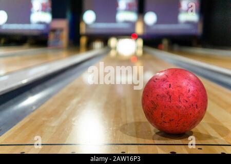 boule de bowling rouge et fond flou dans le terrain de jeu de bowling Banque D'Images