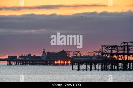 Brighton UK 6 février 2020 - le soleil se lève derrière Brighttons deux piers sur un matin froid et lumineux . Des conditions météorologiques mieux réglées sont prévues pour les deux prochains jours en Grande-Bretagne avant que le temps de tempête ne soit prévu pour arriver pendant le week-end . Crédit: Simon Dack / Alay Live News Banque D'Images