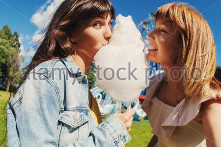 Deux jeunes femmes adultes mangeant des bonbons de coton dans le parc d'attractions. Banque D'Images