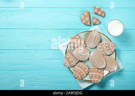 Biscuits de Pâques dans une plaque sur un fond bleu. Œufs de Pâques. Lapins de Pâques. Placer pour le texte. Vue de dessus. Verre de lait Banque D'Images
