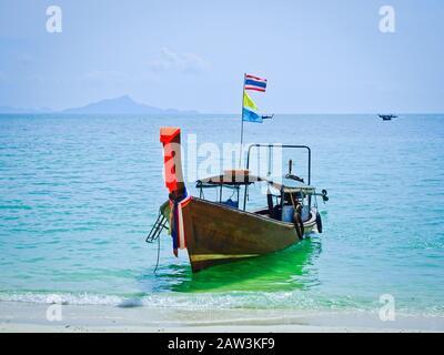 Bateau thaïlandais traditionnel pour les touristes amarrés près de la plage sur le fond de la mer d'Azure. Îles de la province de Krabi, Thaïlande. Un ro