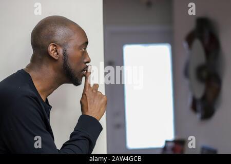 Portrait d'un homme afro-américain avec le doigt sur les lèvres demandant le silence sur fond blanc