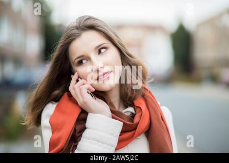Conversation téléphonique. Portrait d'une femme d'affaires sur téléphone portable gai isolé dans de ville focalisée Bruxelles Belgique sur fond Banque D'Images