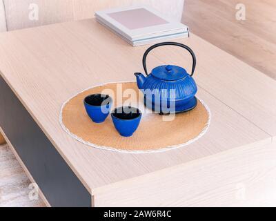 Théière et tasses en céramique chinoise sur une table en bois dans un salon lumineux et confortable au style naturel Banque D'Images