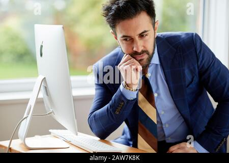 Homme assis à l'ordinateur réfléchi