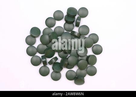 Pilules rondes vertes vue de dessus sur un fond blanc. Comprimés de spiruline, suppléments alimentaires utiles.